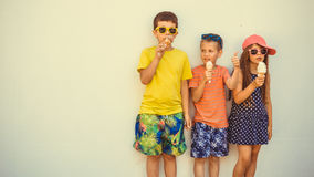 Kids boys and little girl eating ice cream. Kids eating gelato and soft serve ice cream. Boys and little girl in sunglasses enjoying summer holidays vacation stock images