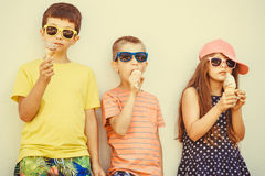 Kids boys and little girl eating ice cream. Kids eating gelato and soft serve ice cream. Boys and little girl in sunglasses enjoying summer holidays vacation Stock Photography
