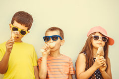 Kids boys and little girl eating ice cream. Kids eating gelato and soft serve ice cream. Boys and little girl in sunglasses enjoying summer holidays vacation Royalty Free Stock Photos