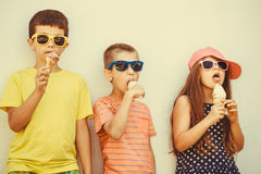 Kids boys and little girl eating ice cream. Stock Images