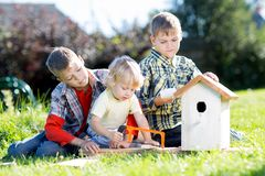Kids making birdhouse together sitting on the grass. Oldest child teaches youngest brother to work with tools. Kids boys making birdhouse together sitting on the Stock Photo