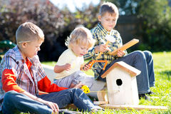 Kids boys play and build birdhouse sitting on green grass Stock Image