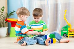 Kids boys play together with educational toys. Two kids boys play together with educational toys Royalty Free Stock Images