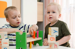 Kids boys playing with toy blocks at home or kindergarten Stock Image