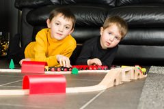 Kids boys playing with wooden trains Royalty Free Stock Images