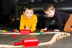 Kids boys playing with wooden trains Stock Photos