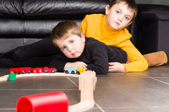 Kids boys playing with wooden trains Royalty Free Stock Photos