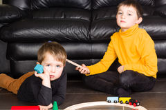 Kids boys playing with wooden trains Stock Image