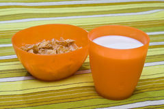Kids' Breakfast. Cereals and milk in kids' orange plastic tableware on a green and white striped tablecloth Stock Photos