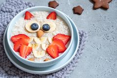 Kids breakfast oatmeal porridge with berries and nuts royalty free stock images