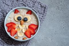Kids breakfast oatmeal porridge with berries and nuts stock photo