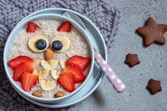 Kids breakfast oatmeal porridge with berries and nuts royalty free stock photo