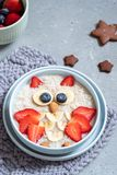 Kids breakfast oatmeal porridge with berries and nuts royalty free stock image