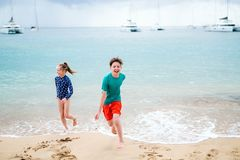 Kids having fun at beach. Kids brother and sister at tropical beach during summer vacation stock photo