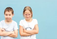 Kids brother and sister twins 8 years old standing with funny faces. On blue background stock image