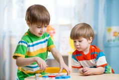 Kids brothers playing together at table stock photography