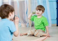 Kids brothers talking with tin can telephone. At home stock images
