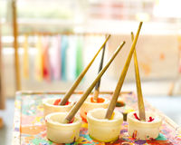 Kids brushes in paint pots. On paint splattered stand Stock Photo
