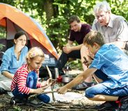 Kids building a camp fire in family camping trip royalty free stock photos