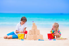 Kids building sand castle on a beach. Kids playing on a beach. Two children build a sand castle at the sea shore. Family vacation on a tropical island. Boy and royalty free stock photos