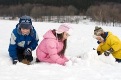 Kids Building a Snow Fort. Three children playing together in fresh snow, building a snow fort and enjoying being outdoors on a cold winter day Stock Image