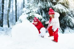 Kids building snowman. Children in snow. Winter fun. Royalty Free Stock Photography