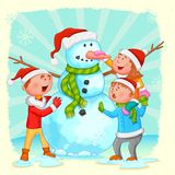 Kids building Snowman for Christmas Stock Photo