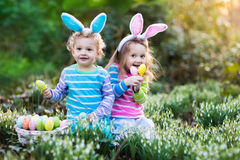 Kids with bunny ears on Easter egg hunt. Kids on Easter egg hunt in blooming spring garden. Children with bunny ears searching for colorful eggs in snow drop stock photo