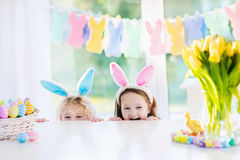 Kids with bunny ears on Easter egg hunt. Boy and girl in bunny ears at breakfast on Easter morning at table with Easter eggs basket. Kids celebrating Easter royalty free stock photo