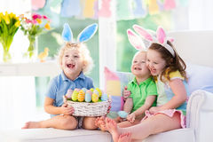 Kids with bunny ears on Easter egg hunt. Kids celebrate Easter. Family, happy little girl, boy and baby in bunny ears on a couch. Children having fun on Easter Royalty Free Stock Image