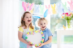 Kids in bunny ears on Easter egg hunt. Little boy and girl in bunny ears holding a heart frame with colorful Easter eggs. Kids celebrate Easter. Children having Stock Image