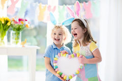 Kids in bunny ears on Easter egg hunt. Little boy and girl in bunny ears holding a heart frame with colorful Easter eggs. Kids celebrate Easter. Children having Stock Photo