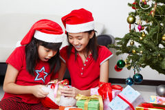 Kids busy opening Christmas present Stock Images