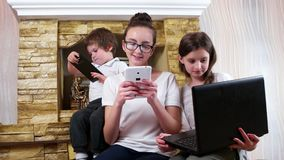 Kids busy playing their electronic devices, little boy looks admiringly in sisters tablets screen stock video footage