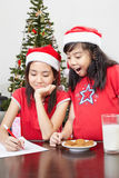 Kids busy preparing letter to Santa Stock Images