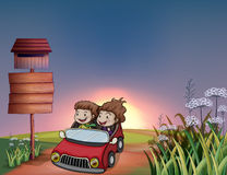 Kids in a car, notice board and a letter box Stock Image