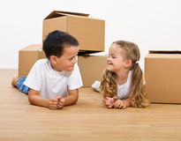 Kids with cardboard boxes on the floor Royalty Free Stock Photos