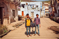 Kids carry a heavy bag on a dusty indian street. BUNDI, INDIA: Unidentified boys carry a heavy bag on a dusty indian street at heat weather in Rajasthan. Bundi Stock Photo