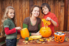Kids carving jack-o-lanterns for Halloween Royalty Free Stock Photography