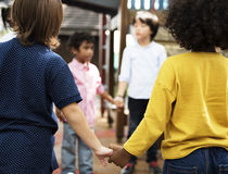 Kids in casual holding hands in a circle royalty free stock photography