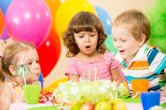 Kids celebrate birthday party blowing candles. Kids celebrating birthday party and blowing candles on cake Royalty Free Stock Image