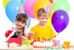 Kids celebrating birthday party and kitten as gift. Happy children celebrating birthday party with opening gift box royalty free stock photos