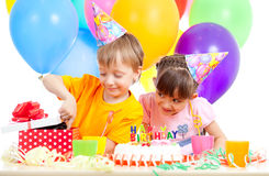 Kids celebrating birthday party and kitten as gift. Adorable children celebrating birthday party and opening gift box stock image