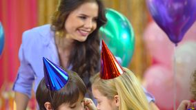 Kids celebrating their birthday with mother and fiends at restaurant. Kids in colorful hats celebrating their birthday with mother and fiends at restaurant stock footage