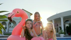 Kids celebrities in swimsuit on summer vacation, little girls lie on inflatable pink flamingo near pool, spoiled rich