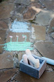 Kids chalks with drawings on stone pathway. In summer stock images