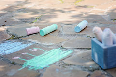 Kids chalks with drawings in summer. On stone pathway stock images