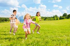 Kids chasing butterfly. With the net, boys and girls, diversity looking, in the park on sunny summer day stock photos