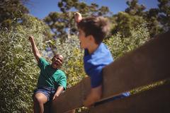 Kids cheering on wooden wall during obstacle course Royalty Free Stock Photo