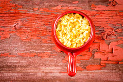 Kids cheese macaroni in clay pot on rustic table Stock Photography